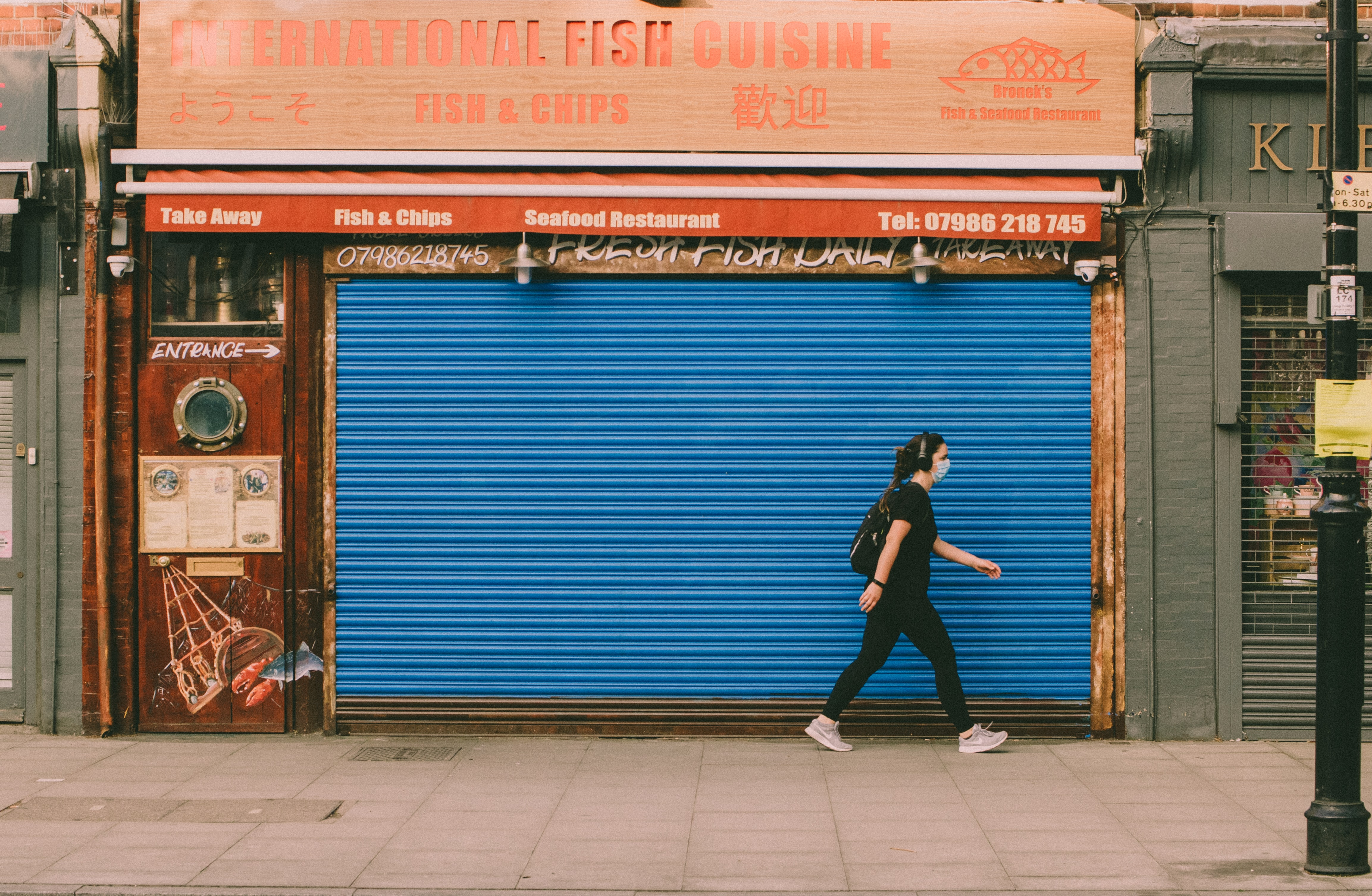 A person with a mask walking by a closed small business