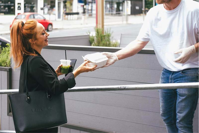 A woman collecting food from a restaurant